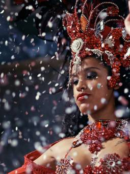 South America, Brazil, Rio de Janeiro, a carnival dancer wearing a feather headdress is showered in confetti