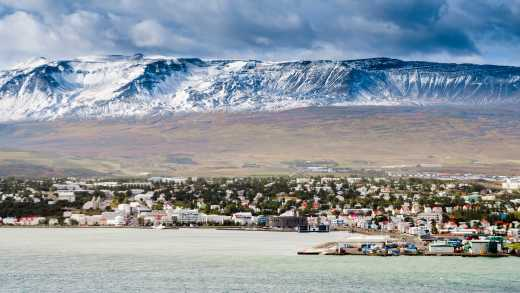 Europe, Iceland, Akureyri seen from offshore with snowy mountains in the background.
