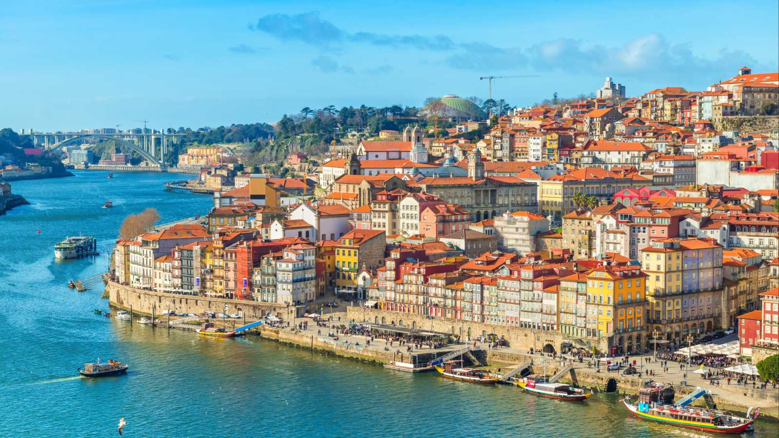 Europe, Portugal, Porto, the Porto skyline seen from  Douro River. Blue sky and brightly lit buildings with red tile roofs.