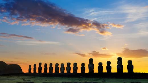 South America, Chile, Easter Island, silhouettes of Moai against the sunset.