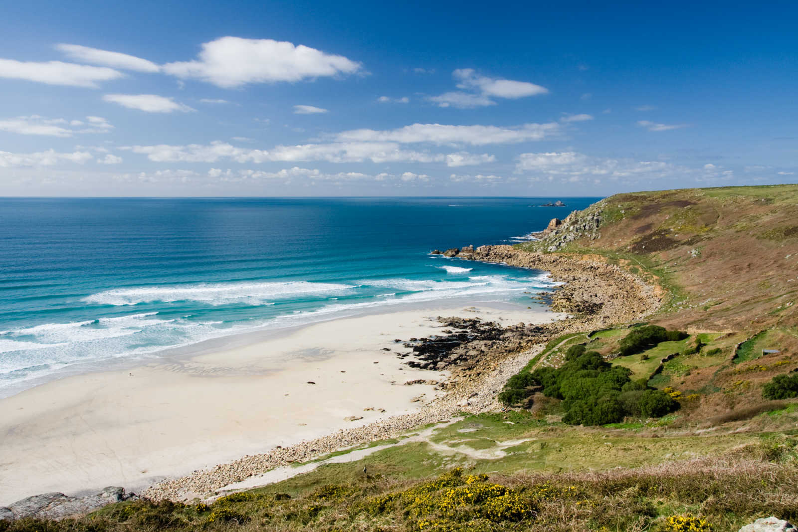 Discover the beautiful Gwenvor Beach, pictured here under blue skies, on a Cornwall vacation