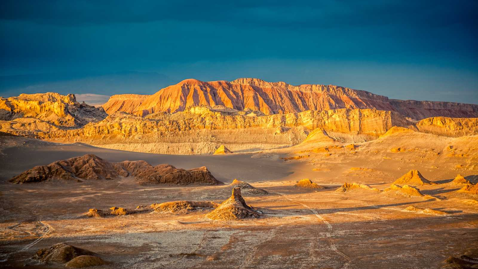South America, Chile, San Pedro de Atacama, a view of Valle de la Luna in the long shadows of the afternoon with a blue sky in the background.