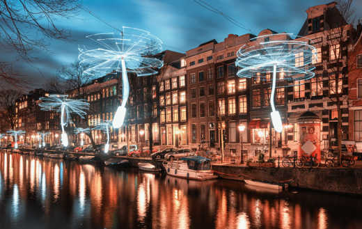 The canals of Amsterdam at night, illuminated by white lights during a festival.