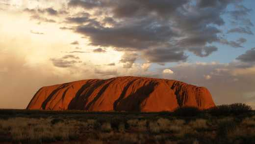 Visit Ayers Rock, pictured here under clouds, on an Outback tour