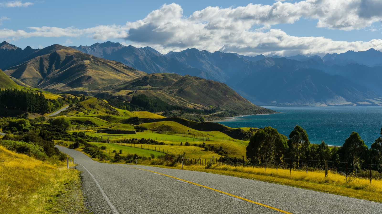View of a highway on New Zealand's South Island, leading to green hills lined by the ocean - discover more on a tour of New Zealand.