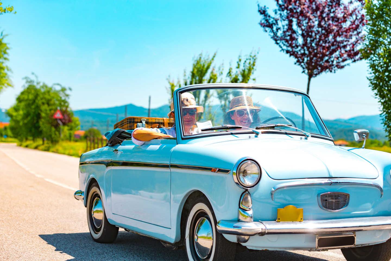 Un couple de seniors pendant un road trip à bord d'une voiture de collection bleu ciel décapotable.