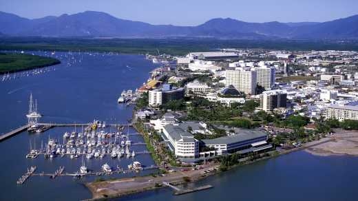 Oceania, Australia, Cairns seen from above surrounded by water and mountains in the background.