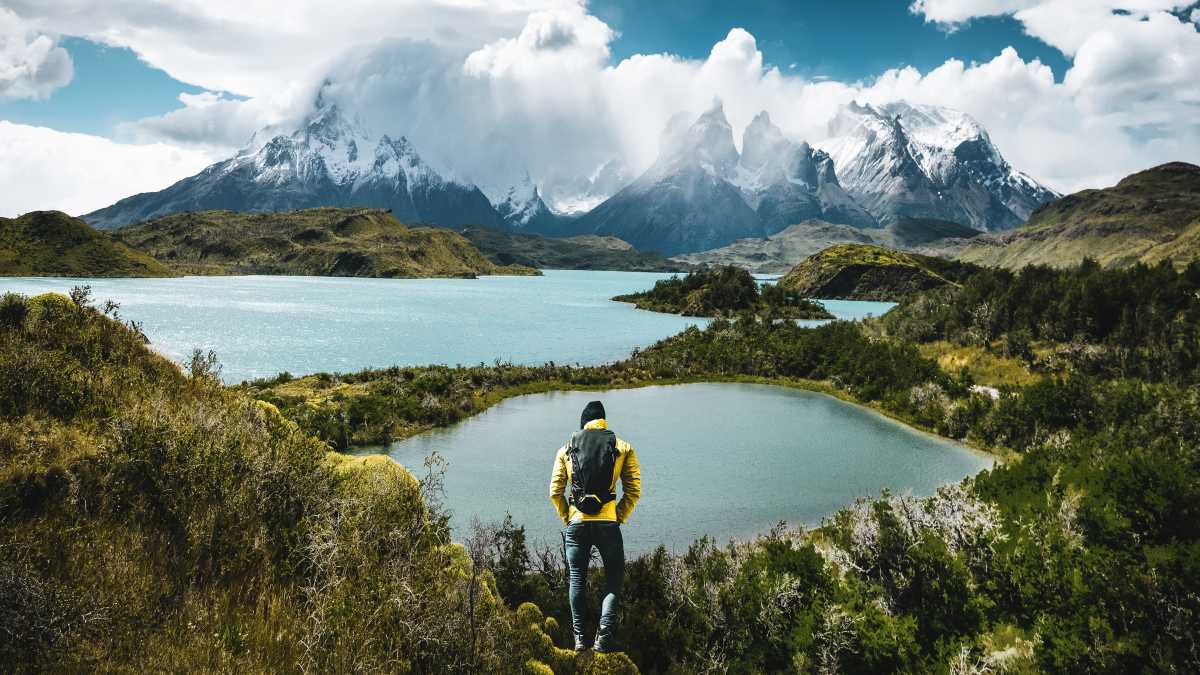 South America, Chile, Patagonia, view of a hiker in Torres del Pain with a sweeping view of snowy mountains, glacial lakes, and forest.