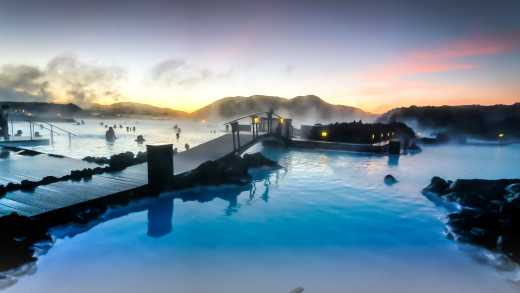 Europe, Iceland, the warm waters of Blue Lagoon steam against a sunset sky.