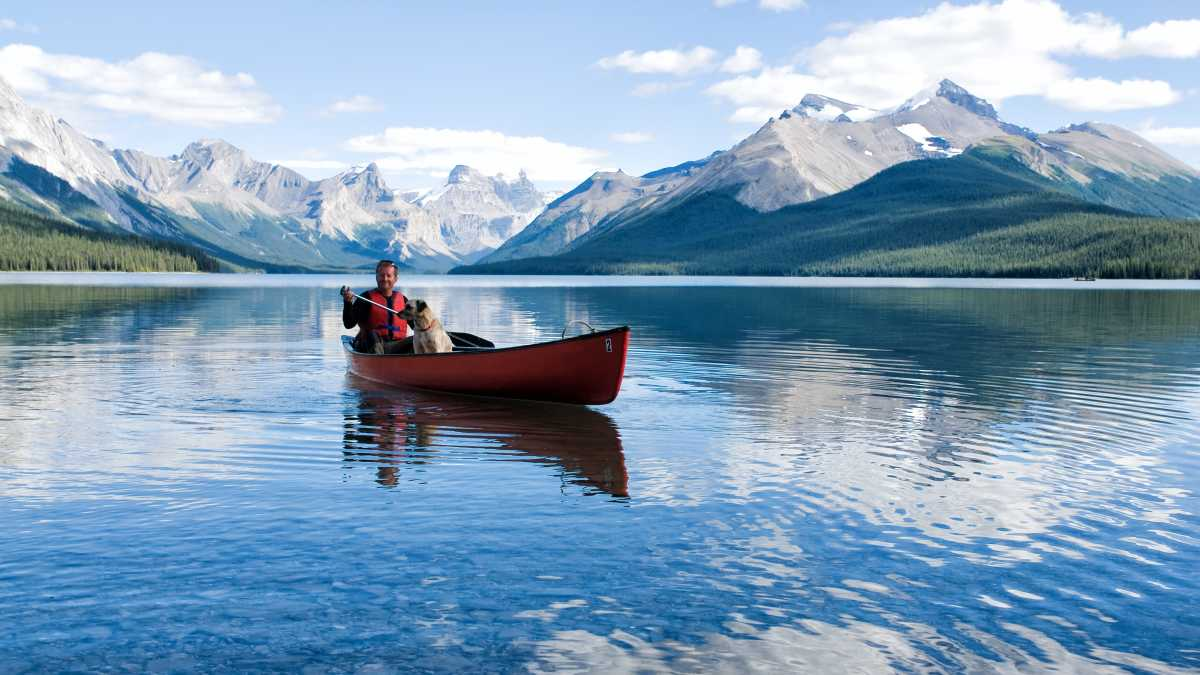 Man met hond in kano op Lake Maligne in de Rocky Mountains, Canada
