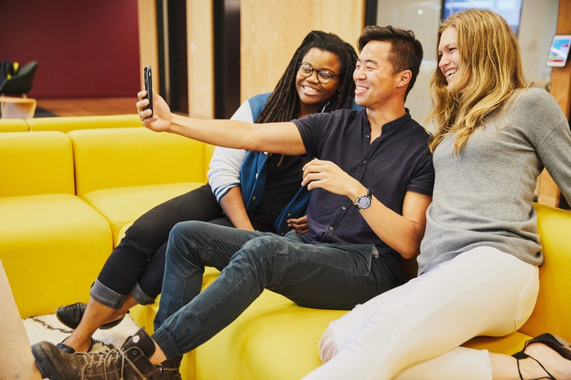 Three Snap Employees on couch looking at phone