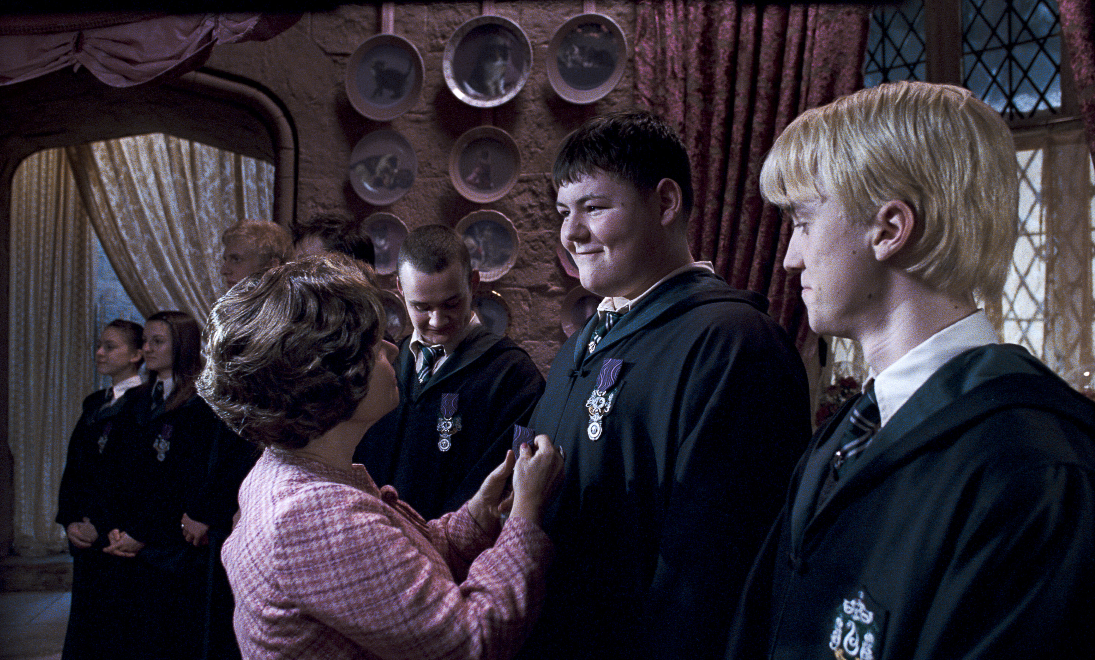 Dolores Umbridge pins a badge to Crabbe's chest as he becomes a member of the Inquisitorial Squad in The Order of the Phoenix