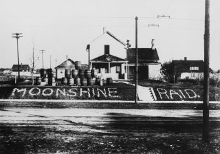 Barrels of  'moonshine' displayed on the front lawn of a house, with a clear declaration of the crime.
