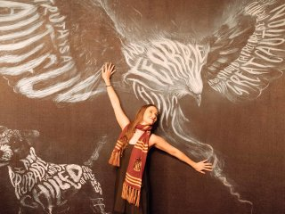 Fan poses outside Patronus Wall, situated in the Lyric Theatre for Cursed Child on Broadway