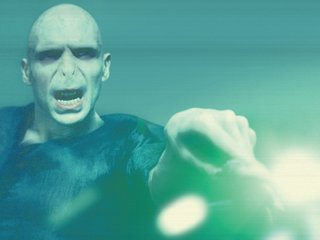 A green beam comes from Voldemort's wand after he casts a killing curse.