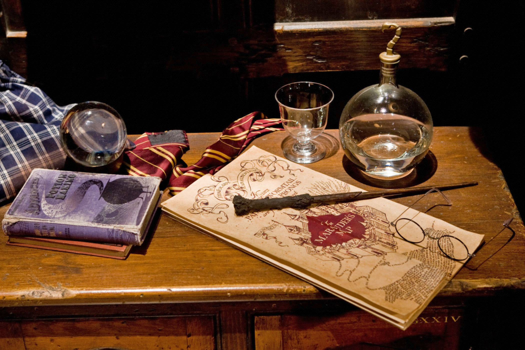 Harry's wand and glasses resting on the Marauders map on a desk