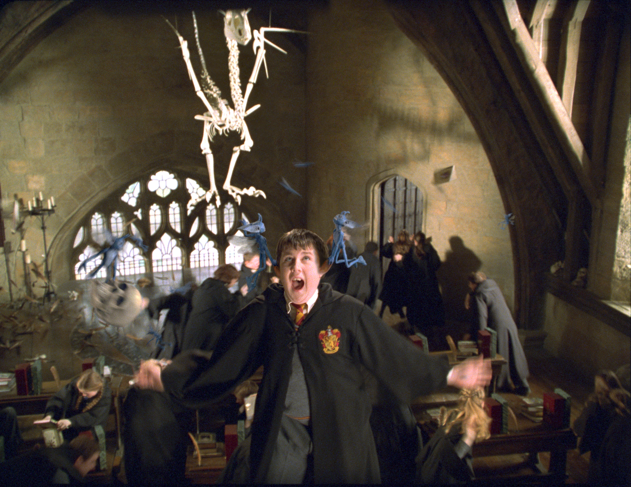 Neville is suspended by the ears by two Cornish pixies, during Defence Against the Dark Arts
