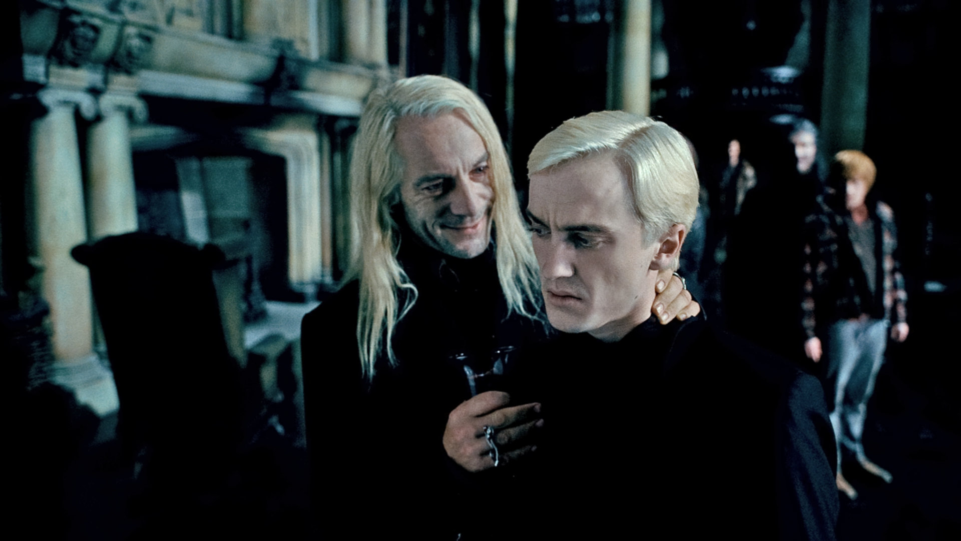 Lucius smiles at Draco and presses his nape affectionately in order to persuade Draco to identify Harry Potter.