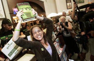 A fan holds up her brand new copy of Half-Blood Prince