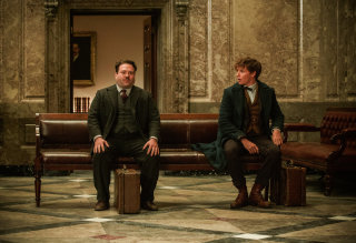 Newt Scamander and Jacob Kowalski sit on benches in the bank with their almost identical suitcases