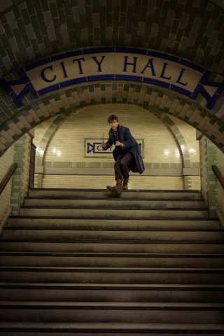 Newt Scamander stands with his wand drawn at the top of the stairs at New York's City Hall subway station