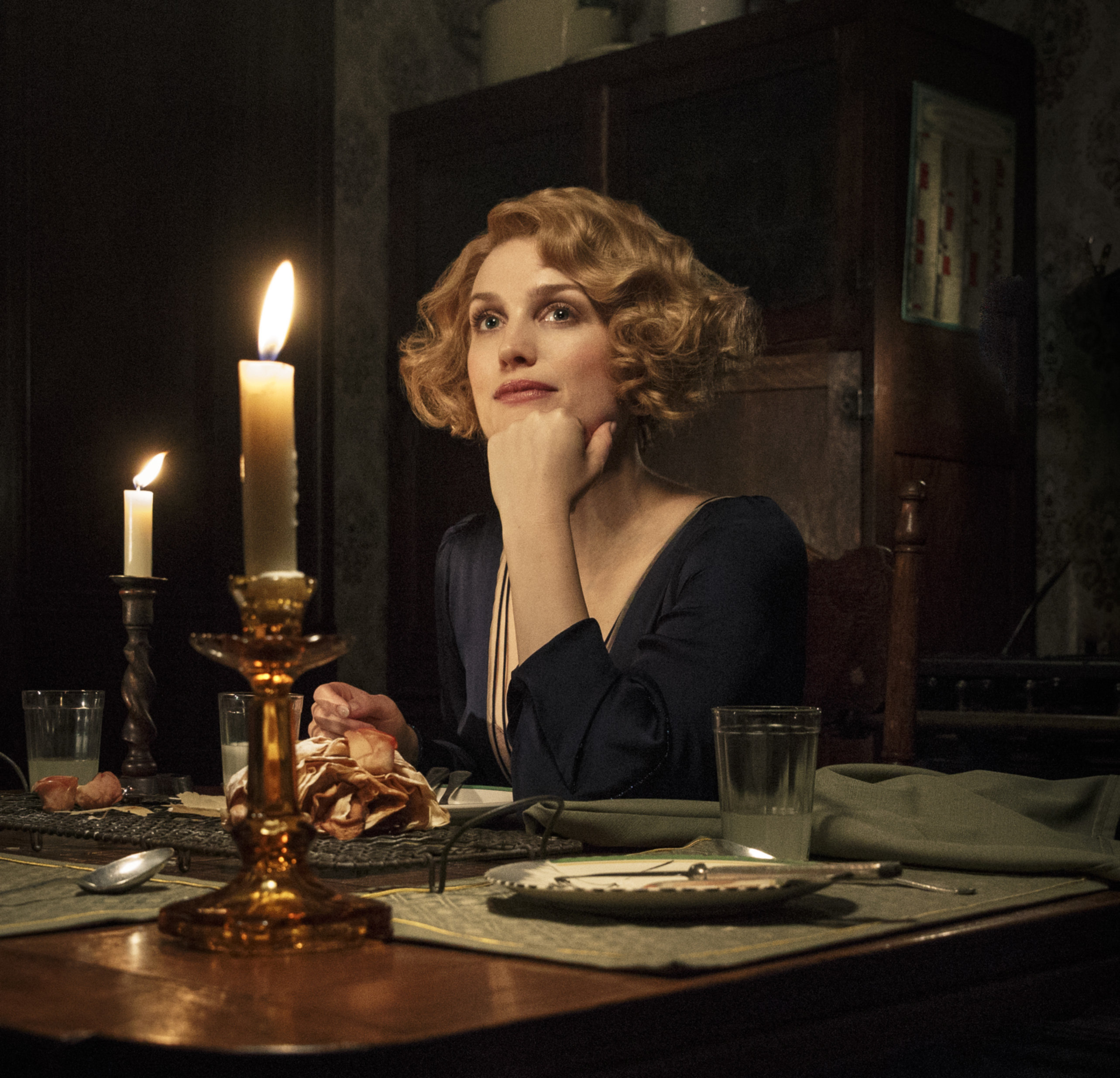 Queenie Goldstien rests her chin on her hand as she sits at a candlelit dinner table