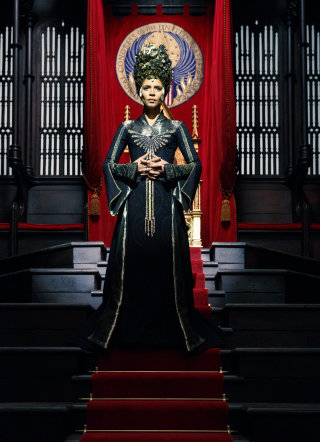 Seraphina Picquery the President of MACUSA stands in front of her President's Throne wearing black and gold robes and an impressive headdress