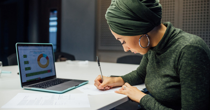 Woman in Green Top and Headwrap Writing on White Table in Front of an Open Laptop