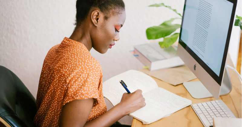 Woman in Orange Writing in Notebook on Wooden Desk
