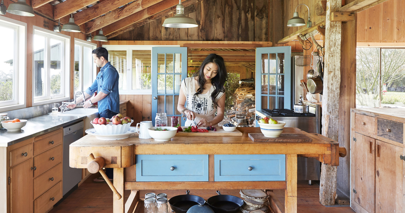 Man and Woman Preparing a Meal in Cabin Style Wood Panelled Kitchen