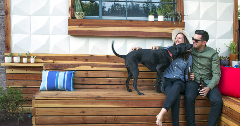 Young Laughing Couple and Black Labrador Retriever Sitting at the Corner of a Wooden Bench