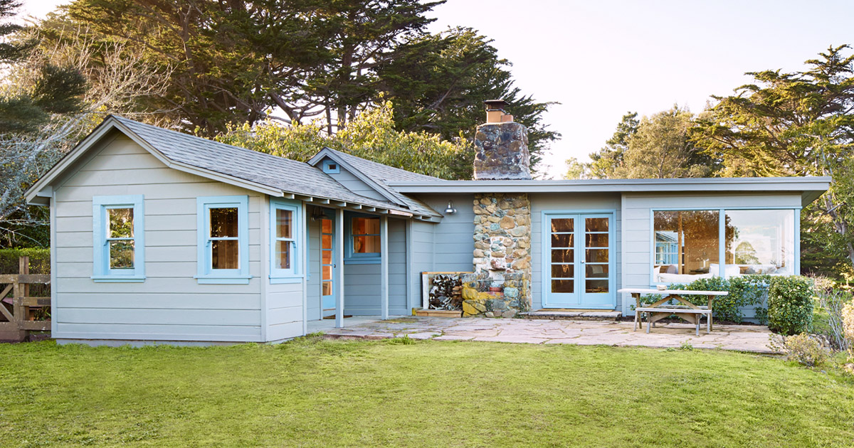 A Light Blue Bungalow Style Home with a Stone Chimney on a Sunny Evening