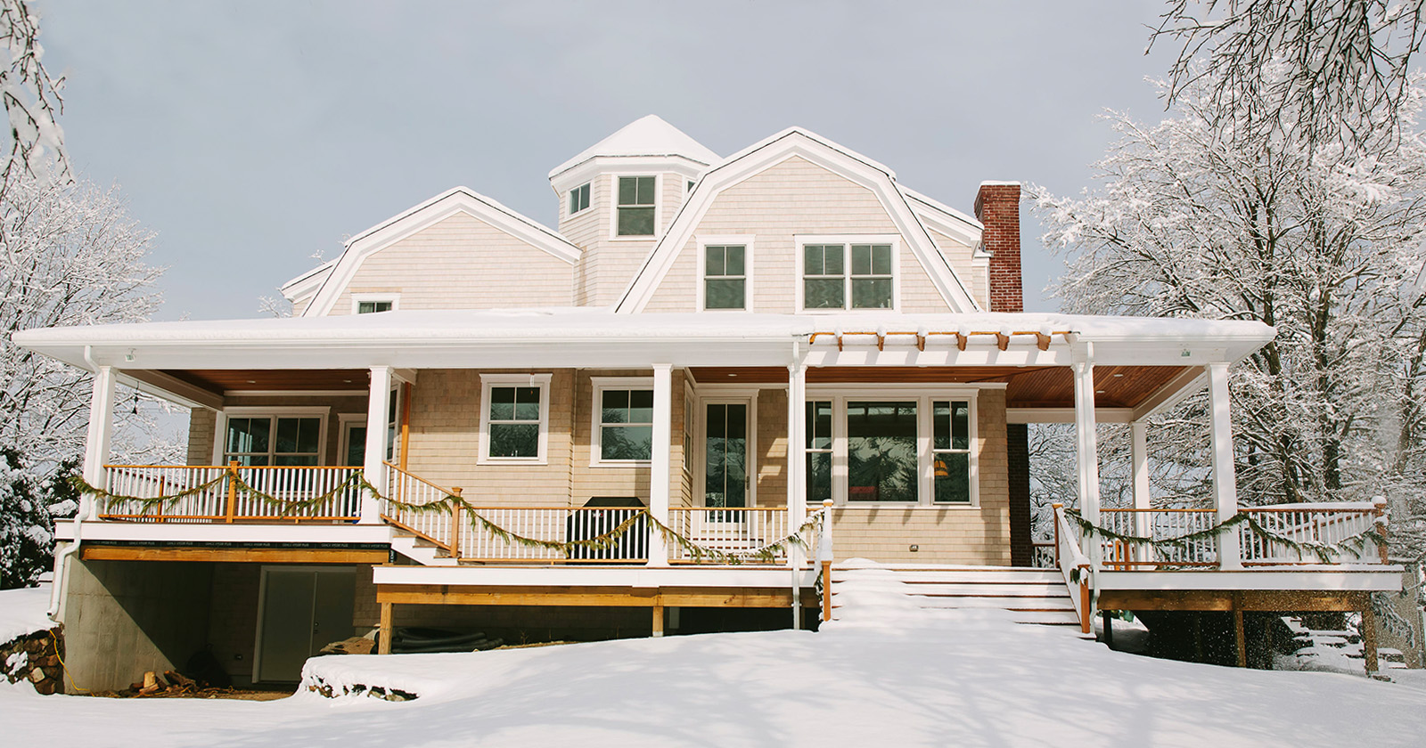 Large Home with Beige Vinyl Siding Surrounded by Snow
