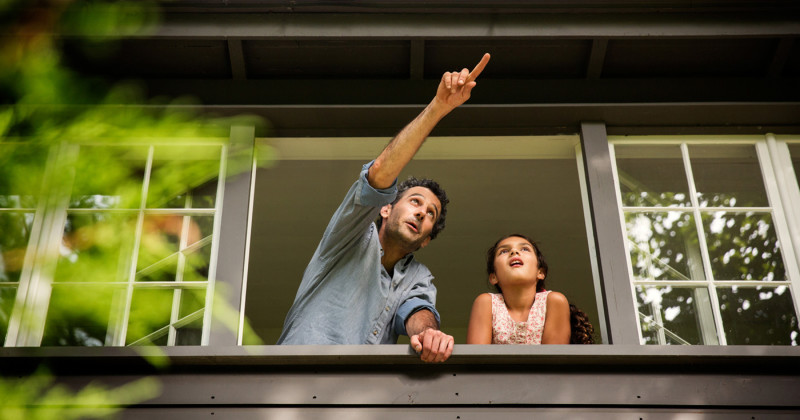 Man Pointing Next to a Child  Outside of a Large Open Window