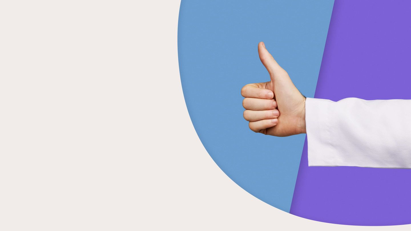 Handing giving the thumbs up gesture on colored background