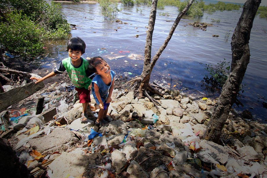 Two boys playing beside a river in the Philippines