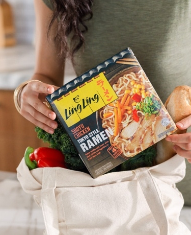 Woman holding a package of Ling Ling shoyu chicken ramen