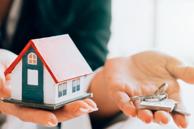 Manos con casa y llaves de vivienda