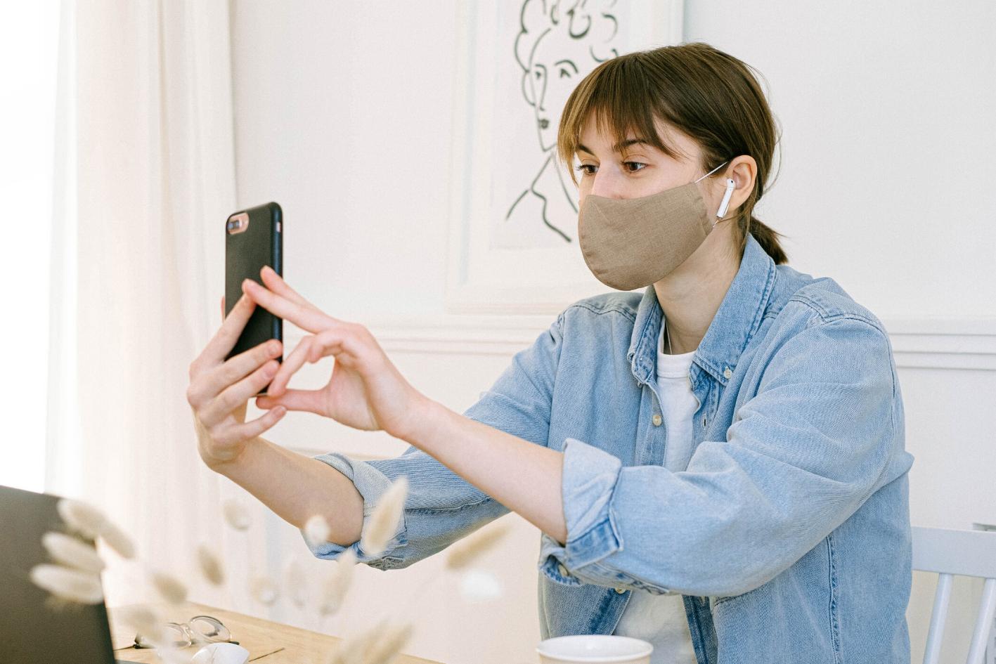 Mujer con tababocas usando su celular