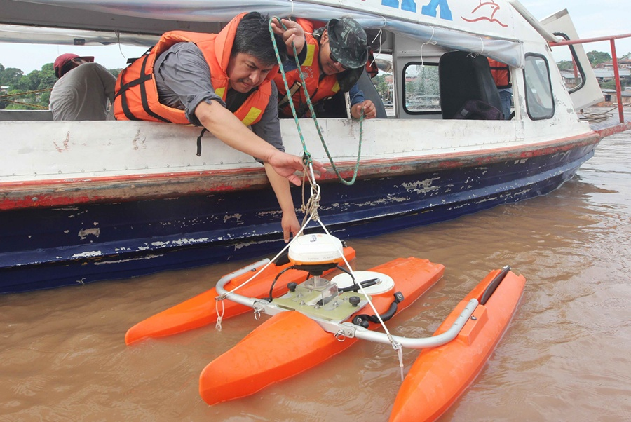 Researchers Releasing Buoy into River - Barbara Fraser