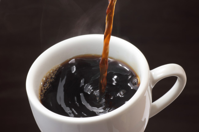 pouring black coffee in a white mug - shutterstock