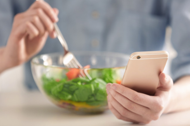Woman eating a salad and logging meal calories Noom app concept - shutterstock