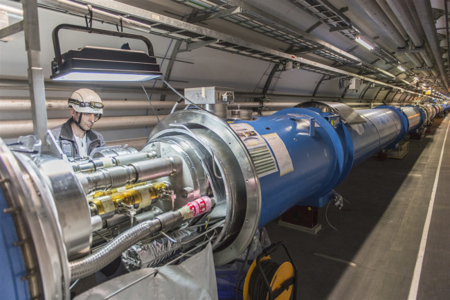 A technician works on the Large Hadron Collider at CERN. (Credit: CERN)