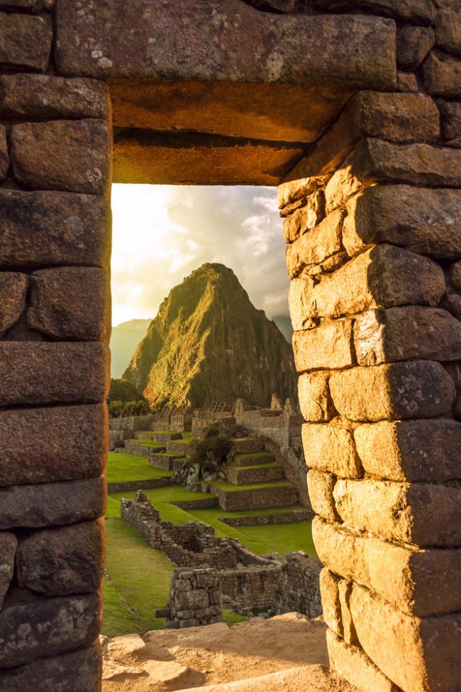 inca doorway framing a mountain - shutterstock