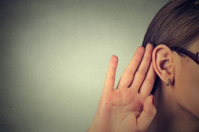 Woman with hand up to her ear, listening hearing - Shutterstock