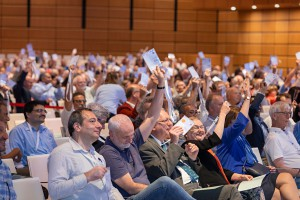 a group of astronomers voting with raised hands