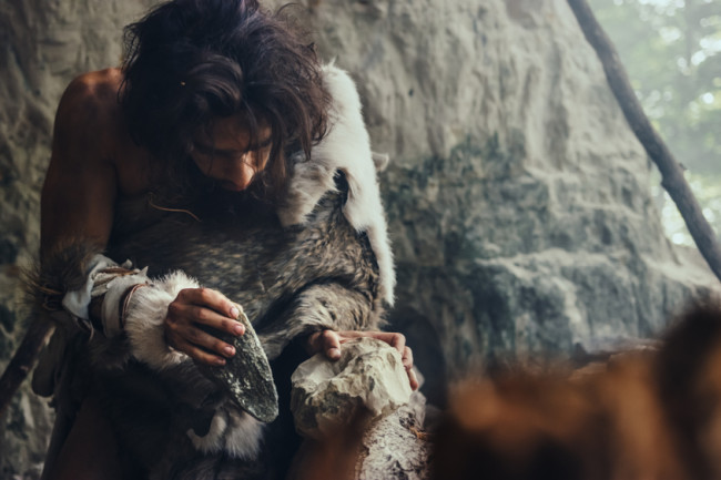 stone age man making a tool - shutterstock