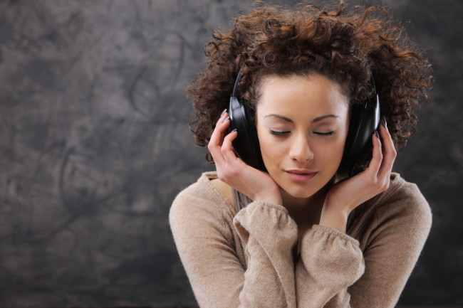 woman with headphones music and a sweater - shutterstock