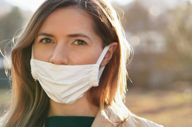 woman wearing mask improperly with nose exposed - shutterstock