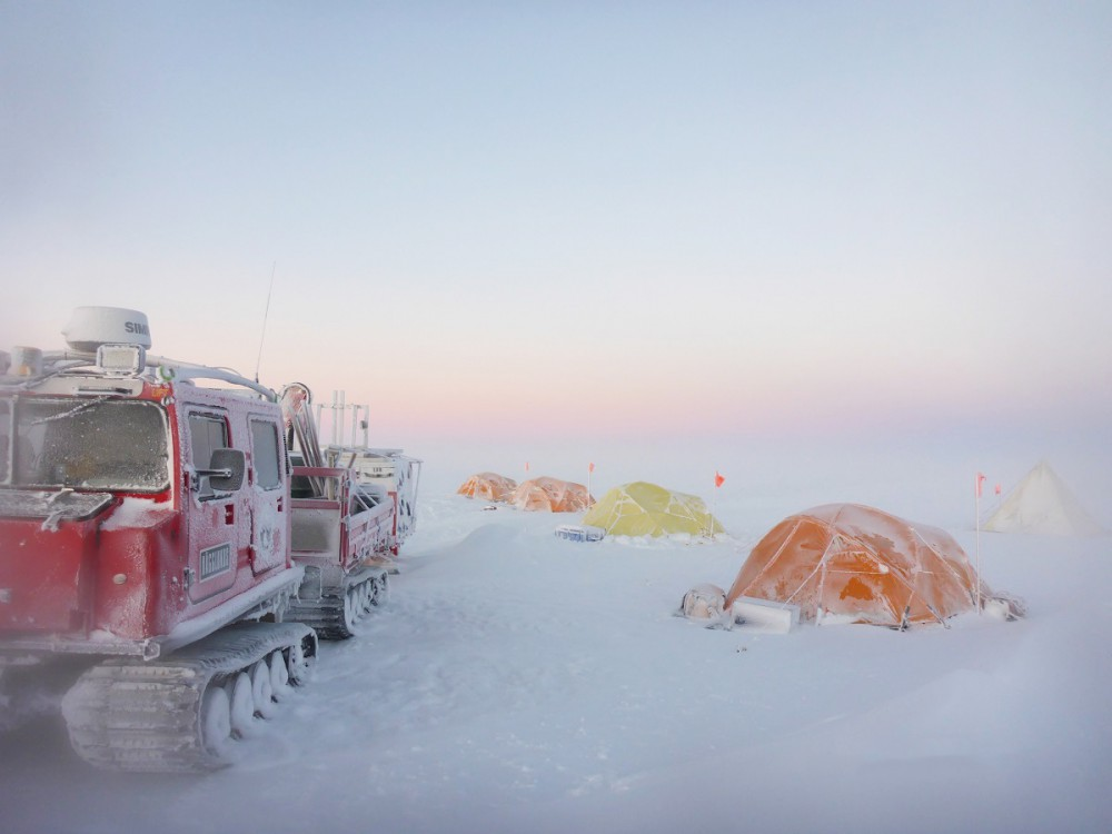 Left, a red Antarctic overland vehicle sits, snow-splattered, on the ice. Right, orange and yellow tents are set up.